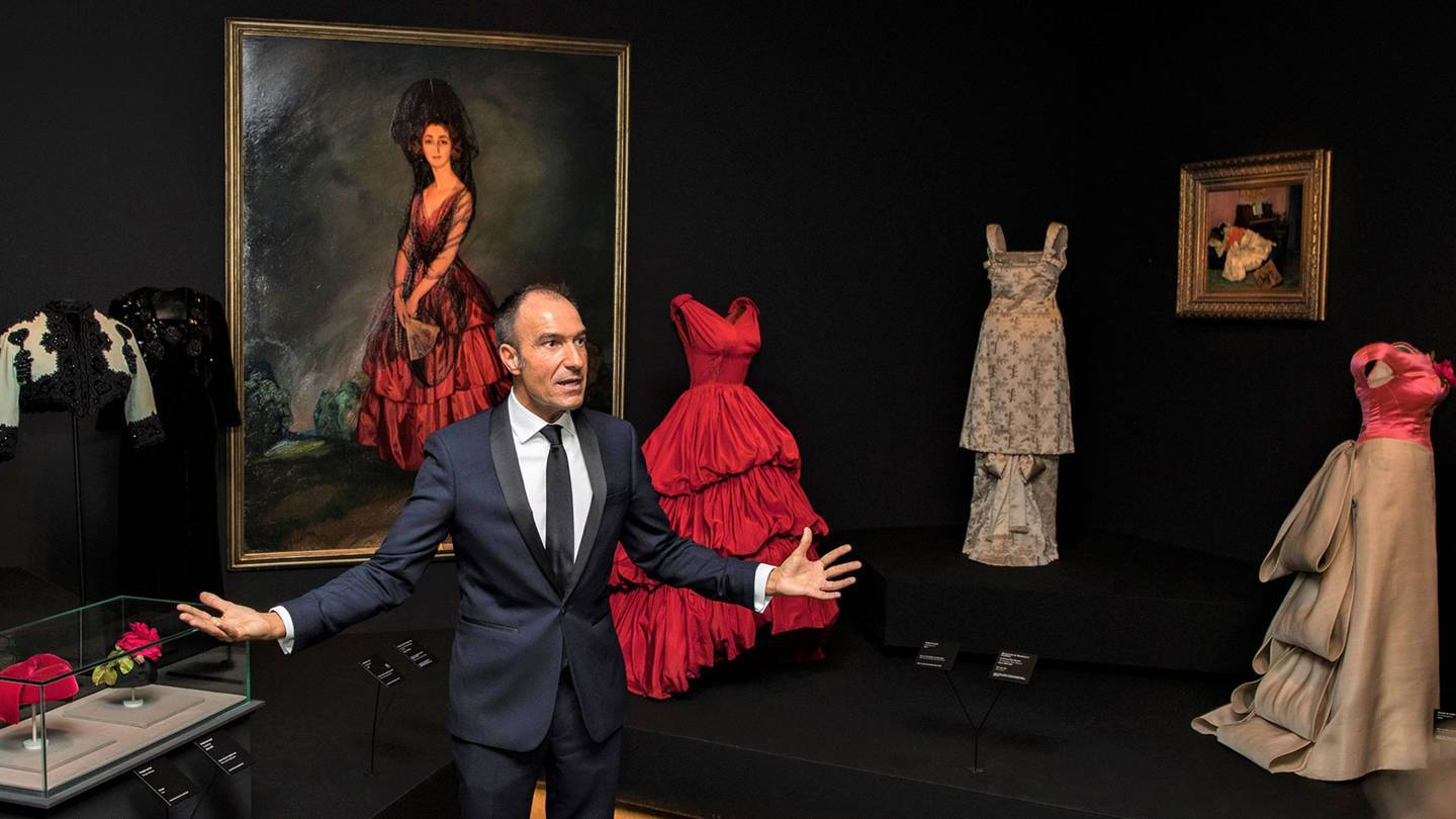 The Balenciaga exhibition curator, Eloy Martinez de la Pera, with the designers scarlet 1952 gown inspired by a 1921 portrait of the Duchess of Alba by Ignacio Zuloaga. Credit: @BORJALAMA