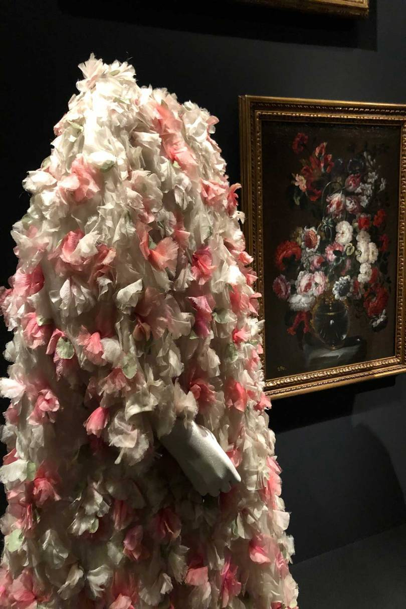A Balenciaga organza evening coat with floral applications (1964) set against the still-life by Gabriel de la Corte, Flowers in a vase (second-half of the 17th century). Credit: NATASHA COWAN