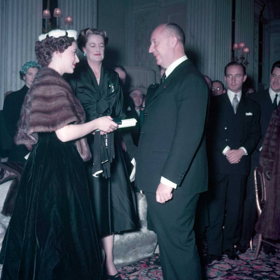 Princess Margaret (left), with the Duchess of Marlborough (second from left), presents Christian Dior with a scroll entitling him to Honorary Life Membership of the British Red Cross after the presentation of his Winter Collection at Blenheim Palace on 3rd November 1954. Credit: 