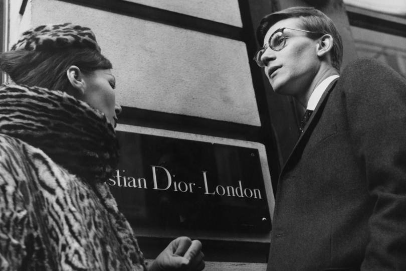 Yves Saint Laurent and a house model in front of Christian Dior London, 11th November 1958. Credit: POPPERFOTO / GETTY IMAGES