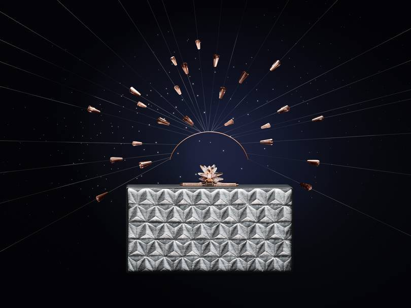 Les Galaxies de Cartier collection metallic-jacquard clutch bag with a pink gold, diamond and milky quartz clasp that transforms into a brooch. Credit: CARTIER