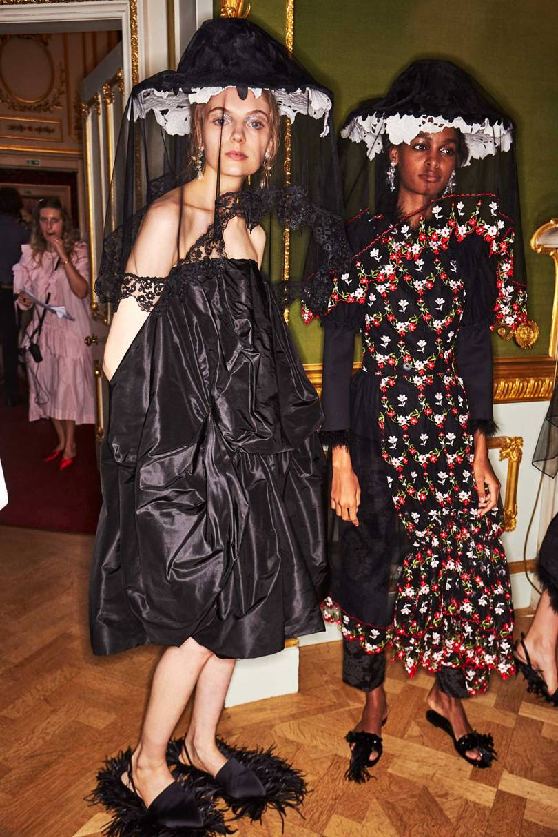 Models backstage at the Simone Rocha Spring/Summer 2019 show wearing her signature accessories for the season – tower hats and fluffy slides and sandals – and the two silhouettes of voluminous or more form-grazing silks and tulle. Credits: KIM WESTON ARNOLD / INDIGITAL.TV